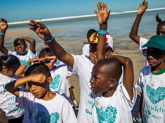 Immokalee second-graders raise their hands to answer questions about what they learned on the beach during Guadalupe Center's Buddy Day at Hideaway Beach on Marco Island on Monday, March 20, 2017. A group of students from the Guadalupe Center's after-school program were paired up with volunteer big buddies for a day of activities at the beach.