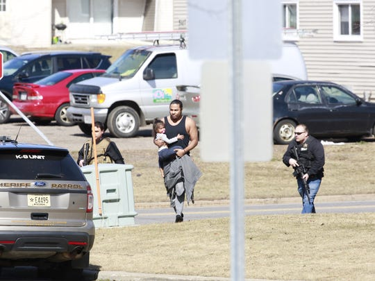 Police officers escort a man with a child from the apartment complex to safety Wednesday on the corner of Aspen Street and Ross Avenue in Weston.