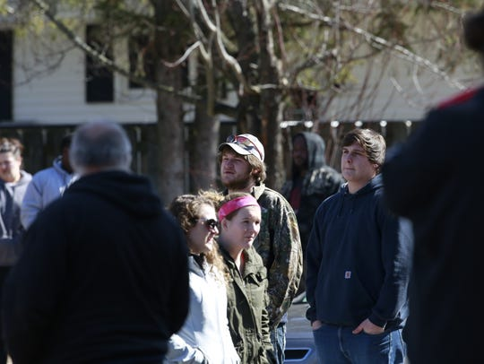 Bystanders watch as numerous law enforcement vehicles
