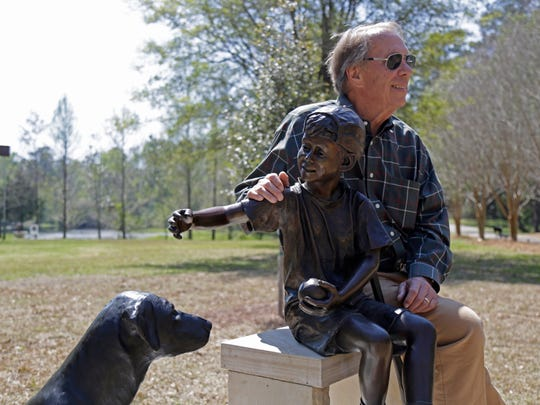 """Sandy Proctor poses with his piece """"Full Team Austin"""" in McCord Park's new sculpture garden March 17."""