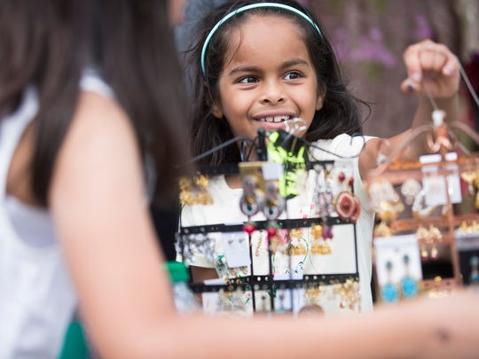 Ranya Asif, 7, smiles while perusing the jewelry offered at a merchandise tent during IndiaFest at Fleischmann Park Saturday, March 25, 2017 in Naples.