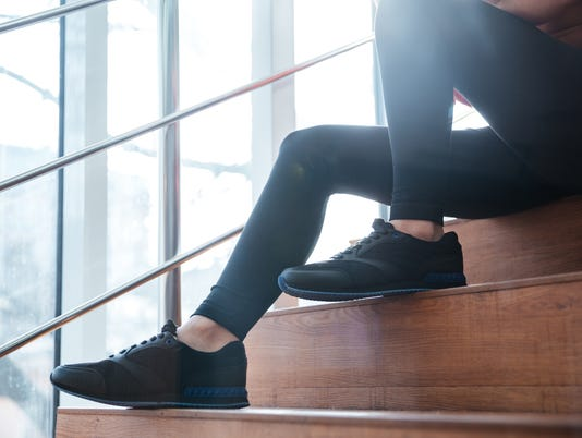 Legs in black leggings of young sportswoman sitting on stairs