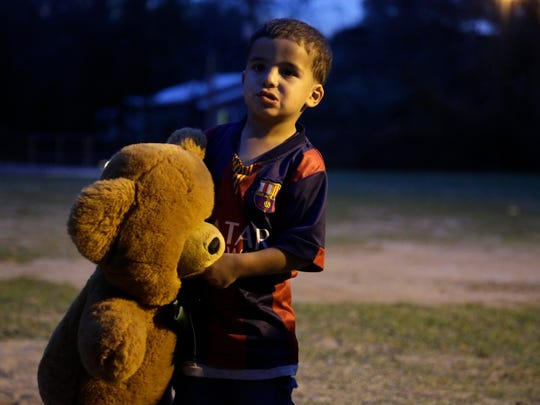 Mohannad Almasri, 2, clutches an oversized teddy bear as night falls on a potluck social held at the Islamic Center of Tallahassee on Old Bainbridge Road March 5.