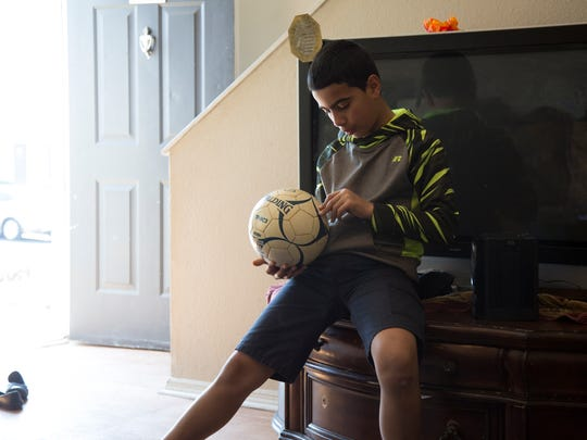 Mohammad Almasri, 11, examines his soccer ball in his living room March 16.