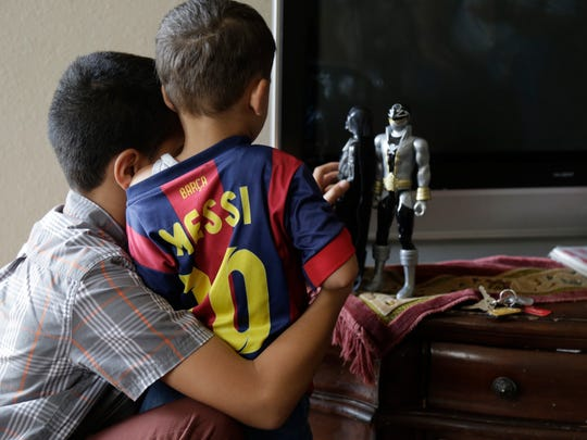 Mohammad Almasri, 11, shows his little brother Mohannad, 2, a pair of action figures in their living room March 5.