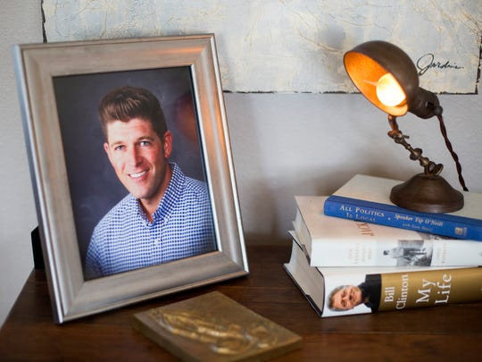 A portrait of their Alex Kuhn sits with some of his books at his parents, Mark and Denise Kuhn's home near Charles City Monday, Feb. 13, 2017.