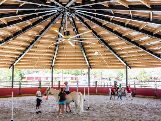 Children participate in a riding lesson in the newly finished riding arena at the Naples Therapeutic Riding Center on Thursday, March 30, 2017. The center just completed a $4 million campus expansion project.
