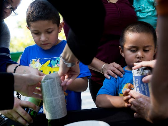 Luis Navarrete, 7, left, and Christian Valencia, 4, with help from zoo volunteers, create handmade flower pots during the Party for the Planet celebration at the Naples Zoo Saturday, April 1, 2017 in Naples.