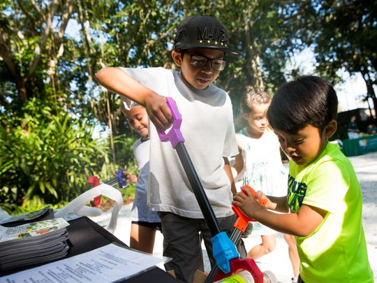 "Ava Deaton, 8, from left, Jaden Decoro, 10, Aydin Deaton, 7, and Caleb Deaton, 4, participate in the ""Trash Challenge"" as they attempt to sort nonrecyclable items from recyclable ones during the Party for the Planet celebration at the Naples Zoo on Saturday, April 1, 2017, in Naples."