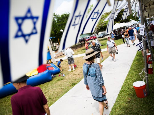Festivalgoers look at the numerous booths during the