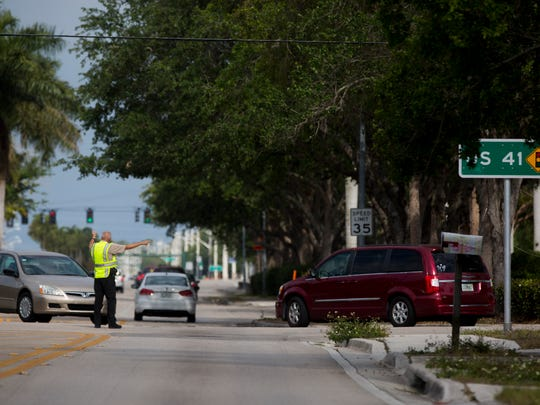 Collier County sheriff;s deputies detour cars driving down 111th Avenue North onto Eighth Street to bypass a small brush fire Sunday, April 2, 2017, in North Naples. The fire was contained soon after it had been reported.