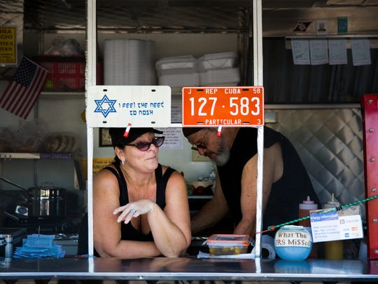 Julie Dana chats with customers as her husband, Ray Garcia, plates a dish behind her on Tuesday, April 4, 2017 at JewBan's Deli Dˆle in the parking lot of the NCH Business Offices and White Elephant Thrift Store in North Naples. The food truck serves Jewish and Cuban food.