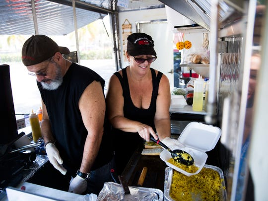 Julie Dana reaches over her husband, Ray Garcia, to fill a container with rice on Tuesday, April 4, 2017, at JewBan's Deli Dale in the parking lot of the NCH Business Offices and White Elephant Thrift Store in North Naples. The food truck serves Jewish and Cuban food.