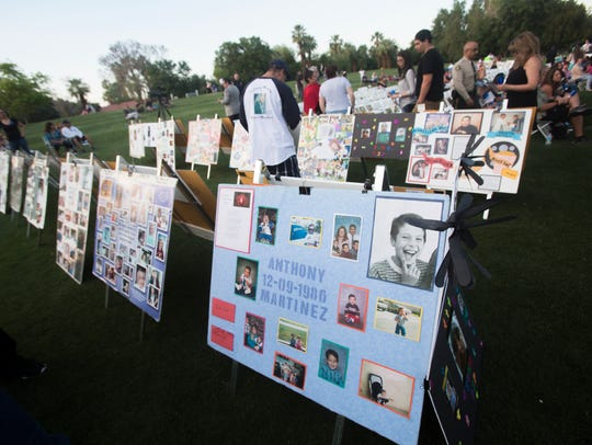 Photos of victims of violence are seen during a vigil