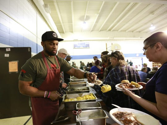 Green Bay Packers' former running back Ahman Green, left, helps to serve food to people Tuesday during the Green Bay Packers Tailgate Tour at the Wausau Salvation Army in Wausau. This is the 12th annual 'Green Bay Packers Tailgate Tour' set to visit fans throughout northern Wisconsin and Upper Michigan.