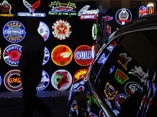 Neon lit signs show off a variety of car-related memorabilia