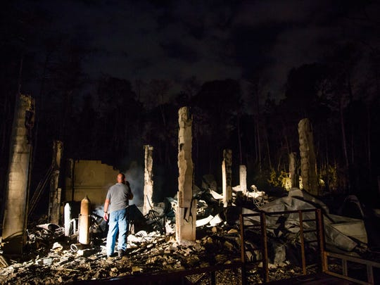 Clifford Richardson, a friend of the Waldecks, shines his flashlight on the wreckage of the Waldeck home on Wednesday, March 8, 2017. The Waldecks lost nearly everything after their home burned down in the brush fire.