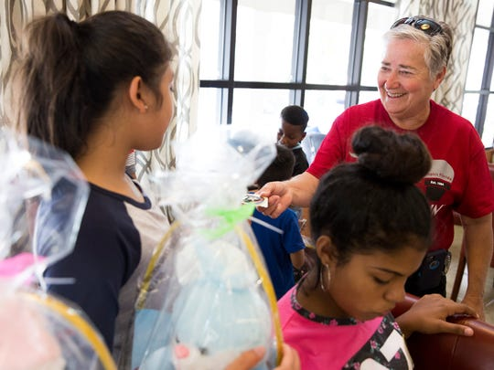 Connie Ledbetter, a deputy with the Collier County Sheriff's Office, hands out stickers to children of the families who lost their homes in the Bear Creek Apartment fire earlier this week at the clubhouse of Bear Creek Apartments Friday, April 14, 2017 in Naples.