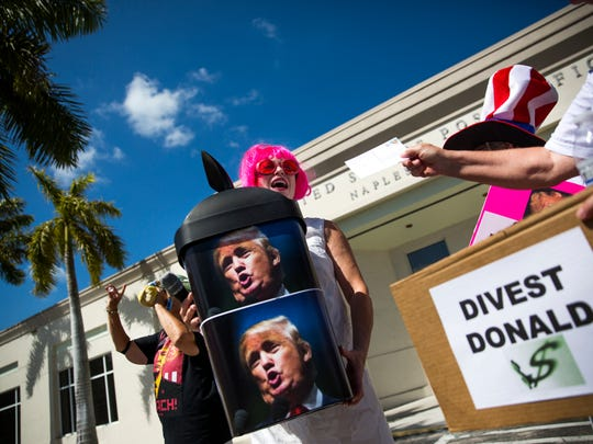 Tamara Paquette holds a bin to collect post cards during the Tax March on Saturday, April 15, 2017 in Downtown Naples. The rally began with participants marching down 8th Ave, across 3rd Street, up 5th Avenue and to the  Downtown Naples Post Office to drop off postcards which were addressed to the President, asking for the release of his tax returns.