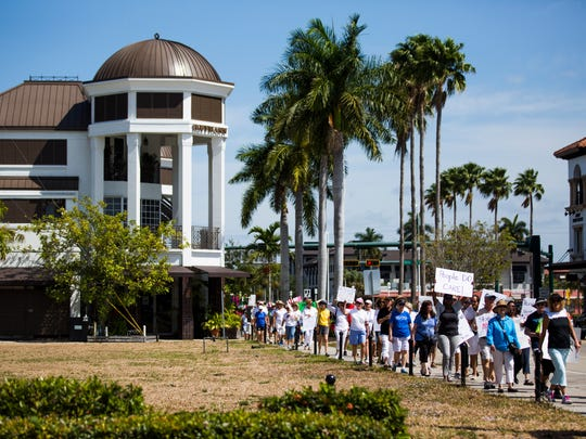 A long line of marchers walk towards the Downtown Naples Post Office during the Tax March on Saturday, April 15, 2017 in Downtown Naples. The rally began with participants marching down 8th Ave, across 3rd Street, up 5th Avenue and to the  Downtown Naples Post Office to drop off postcards which were addressed to the President, asking for the release of his tax returns.