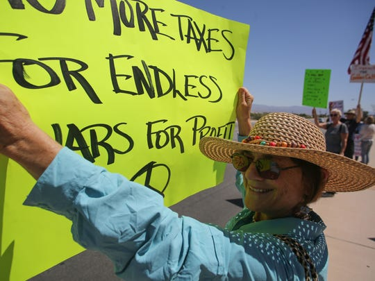Eva Mansell, of Whitewater, waves her sign in protest to passing drivers along Ramon Rd. About two hundred people gather outside the Internal Revenue Service office in Palm Springs to call for President Trump to release his tax returns on Saturday, April 15, 2017. The protest is part of a nationwide Tax March to get President Trump to release his returns.