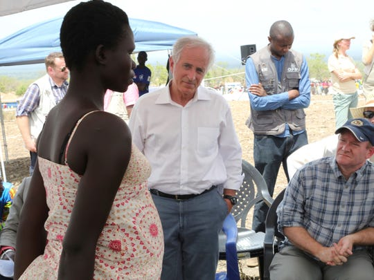 Sens. Bob Corker, center, and Chris Coons, right, speak with a South Sudanese refugee during a group discussion at the Bidi Bidi refugee settlement in northern Uganda on April 14, 2017. The U.S. senators are proposing to make American food aid more efficient after meeting with victims of South Sudan's famine and civil war.