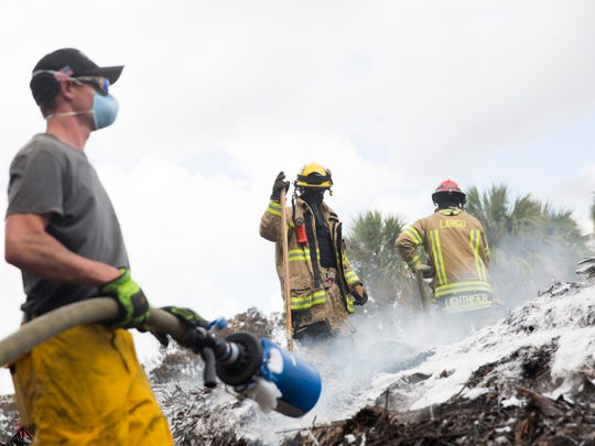 Firefighters with Pasco County and Largo Fire Rescue, both members of the Pinellas County Strike Team, work to put out a mulch fire at Case Landscaping off Smith Road on Monday, April 24, 2017, in Golden Gate Estates.