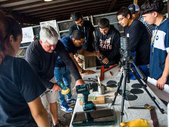 High school students watch a glass-cutting demonstration at a trades fair at Collier County Fairgrounds on Thursday, April 27, 2017. Representatives from local businesses talked with students about opportunities in trades and skills jobs such as construction, carpentry and engineering.