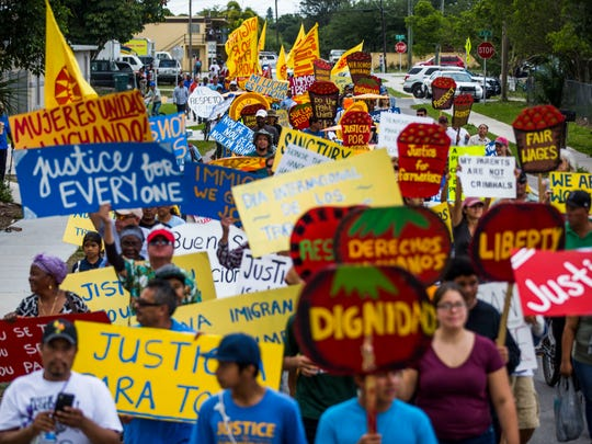 Residents march through the streets of Immokalee for International Workers' Day on Monday, May 1, 2017.