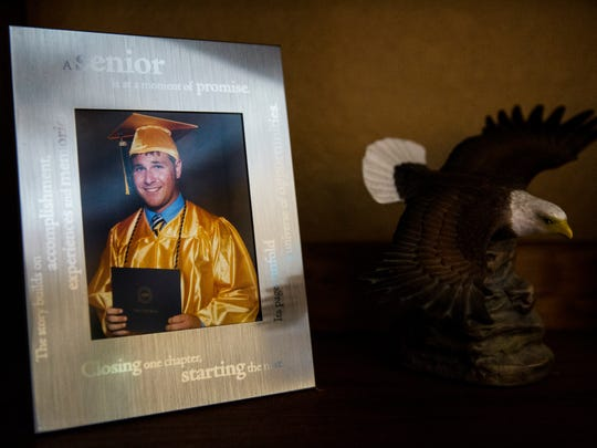 Marc Newberry's high school graduation photo sits on a shelf at his home in Naples on Wednesday, May 3, 2017. Newberry, 20, was killed in a canal boat crash on April 28.