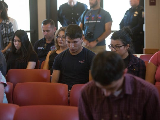 Family and friends of New Mexico State University students, faculty and staff bow their heads during a prayer at a memorial service held Wednesday, May 3, 2017 at the Spiritual Center on campus.