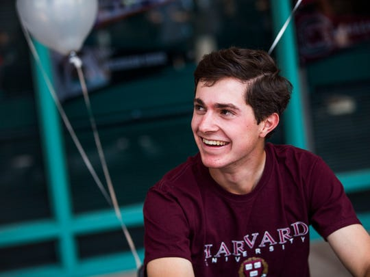 Senior Peter George is celebrated by his peers during an academic signing day ceremony at Gulf Coast High School on Thursday, May 4, 2017. George will attend Harvard University in the fall.