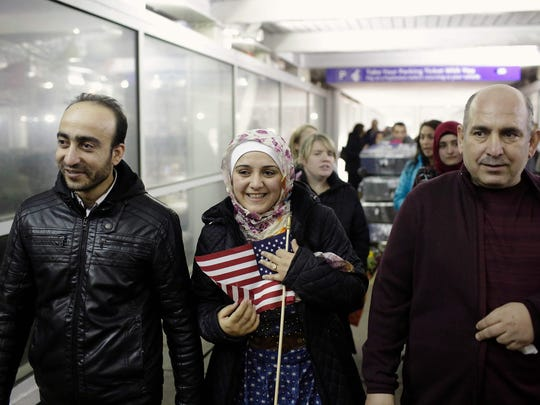 Syrian refugee Baraa Haj Khalaf holds an American flag alongside her husband and father at Chicago's O'Hare International Airport in early February after gaining entry to the U.S. She and her family had been blocked after President Trump signed his original executive order in January.
