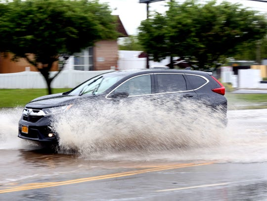 Cars navigate the flood waters on Route 59 near Palisade