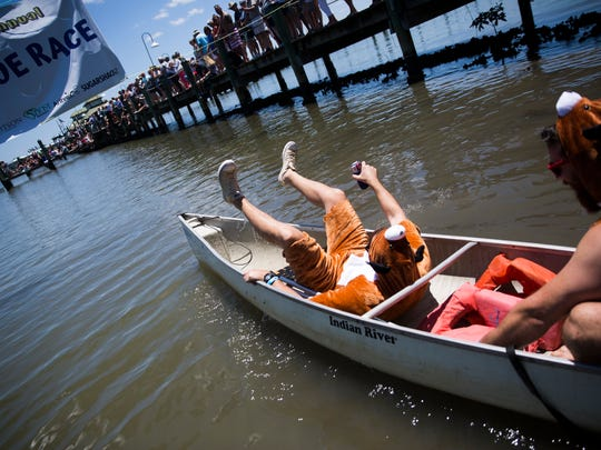 "Marc Havig falls backwards as he and his partner, Colin Hurd, make their way to the starting line for the ""Ambitious Amateurs"" canoe race during the 41st annual Great Dock Canoe Race at the Naples City Dock at Crayton Cove on Saturday, May 6, 2017. This years races featured a ÒBack to the FutureÓ theme."