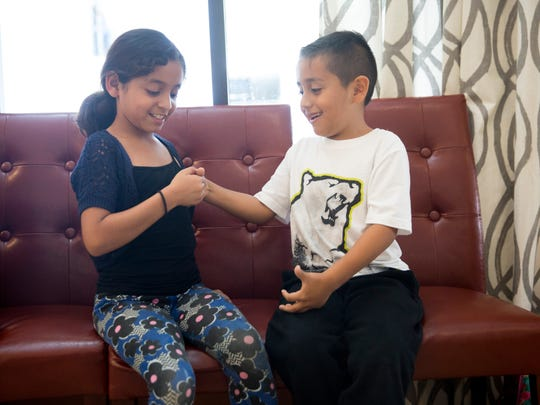 Erick Garibay, 5, and his sister Michelle, 8, play a game of thumb war while patiently waiting for their shoes donated by the Rotary Club of Naples Bay at the Bear Creek Apartments in North Naples on Monday, May 8, 2017. The siblings' family lost their home in the Bear Creek Apartments fire last month.
