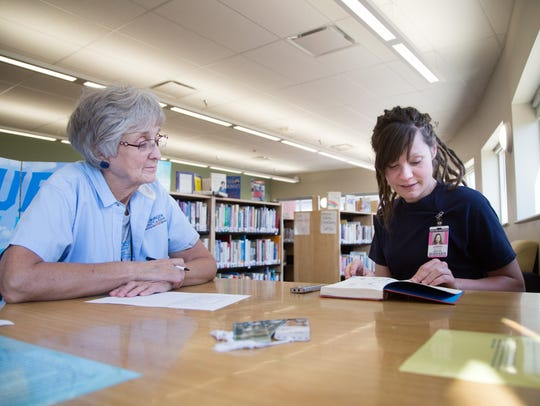 Inmate Kristine Gordon reads a book with Marilyn Clauss