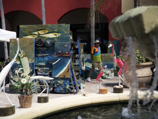 Artist Mitch Billeter (Fishman) of Naples walks around his art display during the Left Bank Art Fest at the Esplanade Shoppes on Marco Island in this file photo.