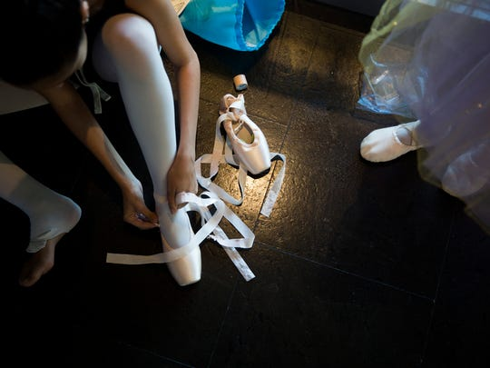 """Jessica Garciduenas, 16, performing as the Lilac Fairy, slips on her ballet pointe shoes in preparation for the Naples Ballet rehearsal of """"Sleeping Beauty"""" on Monday, May 8, 2017, in Naples."""