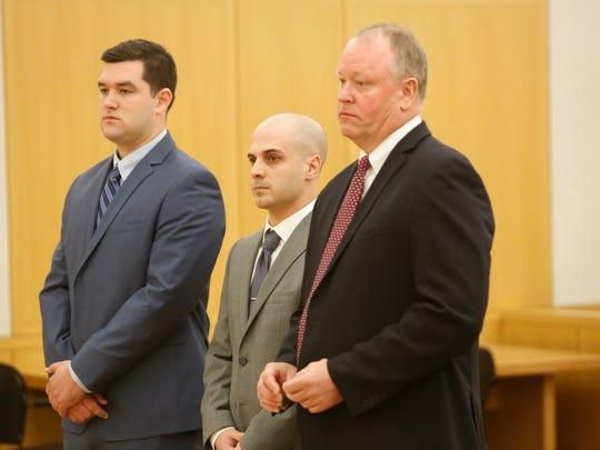 New Rochelle Police Officer Harry Kyreakedes, center,