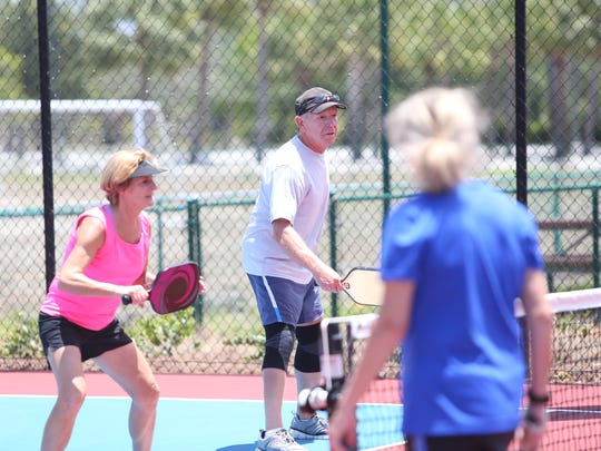 Chris DeWitt, left, and Ron Banks prepare to return a volley at the newly opened Bonita Springs YMCA pickleball courts.