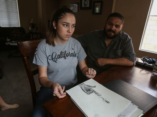 Alex Reyes looks on as his daughter Valerie Reyes, 18, shows her artwork on April 7, 2017 in Coachella. Valerie attempted suicide two years ago. She said that art is a way for her to escape daily stresses.