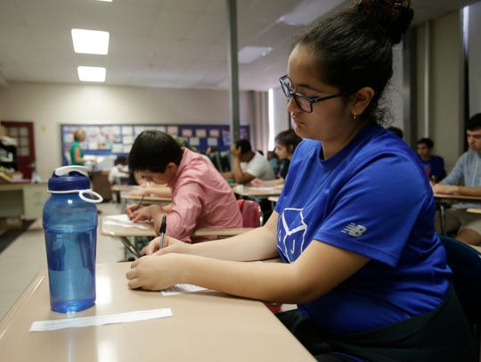 Jessilyn Pereira, 14, fills out a form to participate