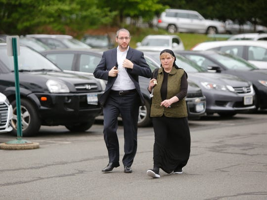 Yitzchok Ullman, councilman and deputy supervisor for the Town of Ramapo, and Mona Montal, head of the purchasing department, walk into the Ramapo Town Hall in Airmont on May. 22, 2017.