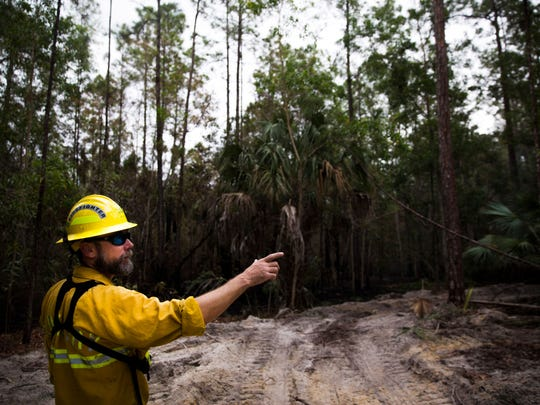 Joe Zwierzchowski, mitigation specialist for the Florida Forest Service, explains the importance of containment lines on Sunday, April 23, 2017 in Golden Gate Estates.