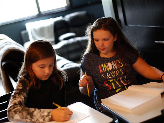 Berkley Maschka, 9, helps brother Creighton, 11, with a math problem Wednesday, May 24, 2017, during a home-school lesson in Urbandale.