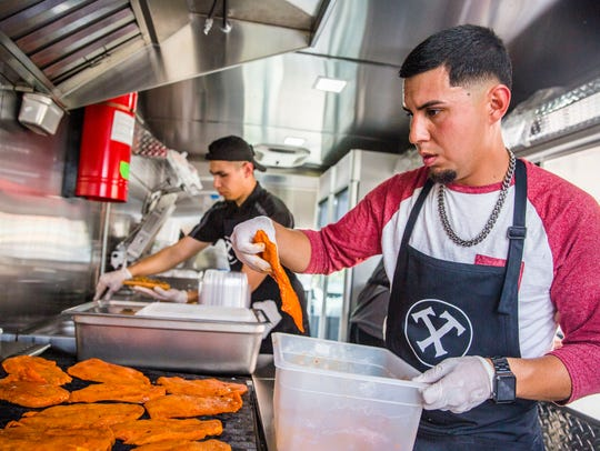 Brothers Gabriel, left, and Luis Trejo prepare food
