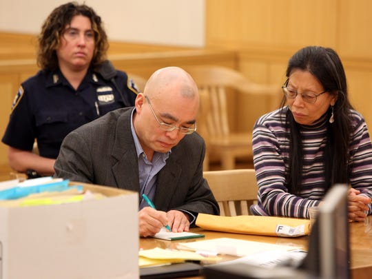Hengjun Chao, left, writes something down as a Mandarin interpreter looks on during the first day of his trial for trying to kill his former boss, Dr. Dennis Charney, at Lange's in Chappaqua last summer, June 5, 2017 at Westchester County Courthouse in White Plains.