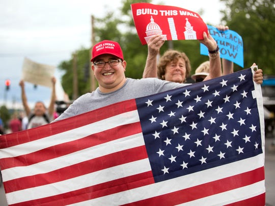 """Houston Crawford, of Eastgate, carried a flag to support President Donald Trump during his remarks at the Rivertown Marina in the East End. Trump was talking about infrastructure. Both pro Trump supporters and those against him, stood side by side as his entourage drove by on the way to the marina. Crawford, who's a firefighter, said Trump's done well with police and fire. """"That's where he had me."""""""