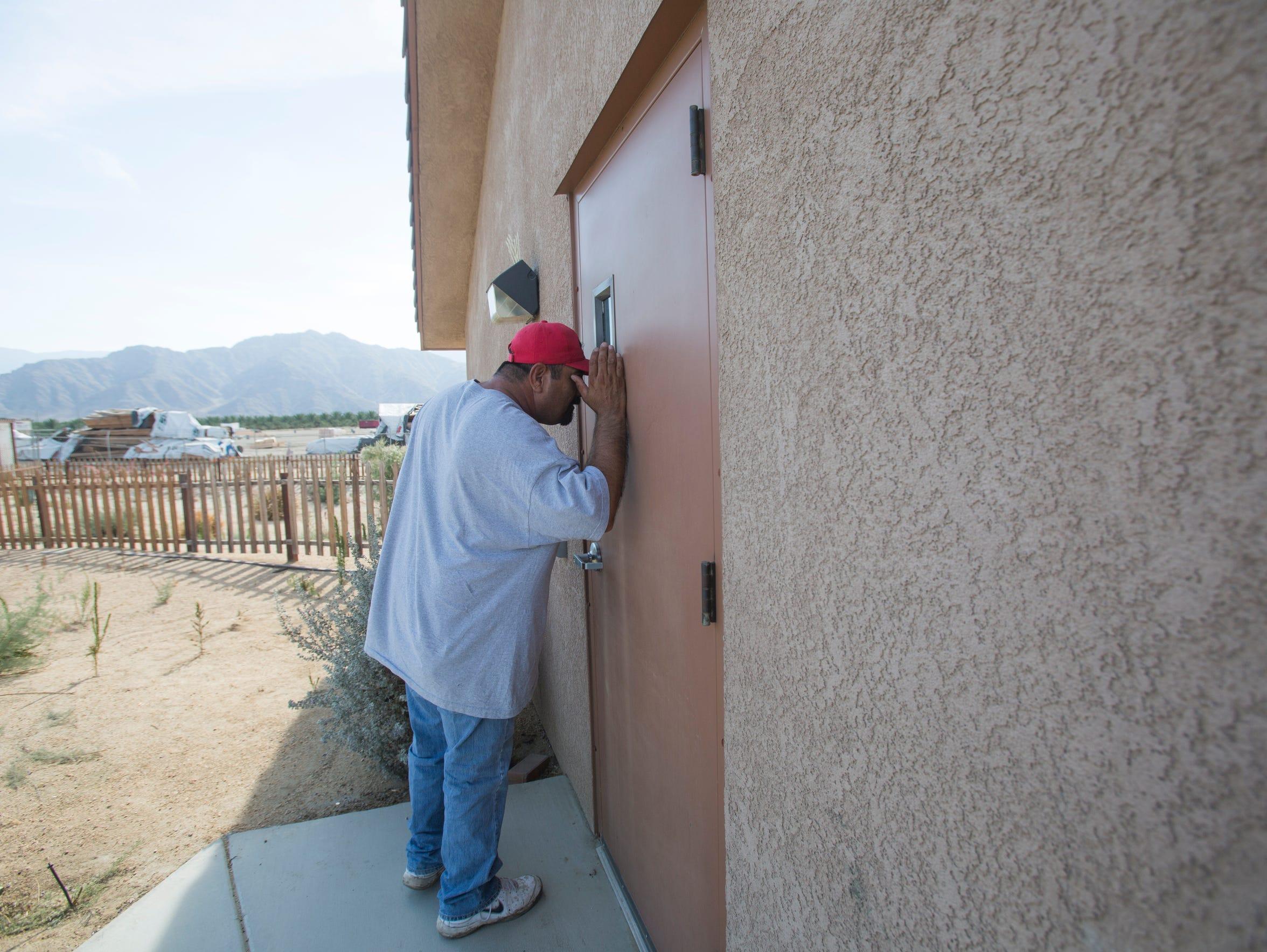 Martin Zavala looks through a window in housing that